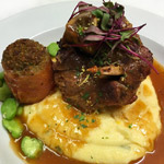 Pork Osso Buco with pan juices, mascarpone / parmesan polenta, pesto stuffed roma tomato, fava beans